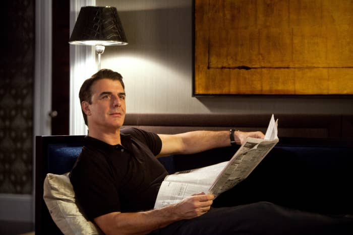 Chris Noth sits on a couch and reads the newspaper in Sex and the City 2