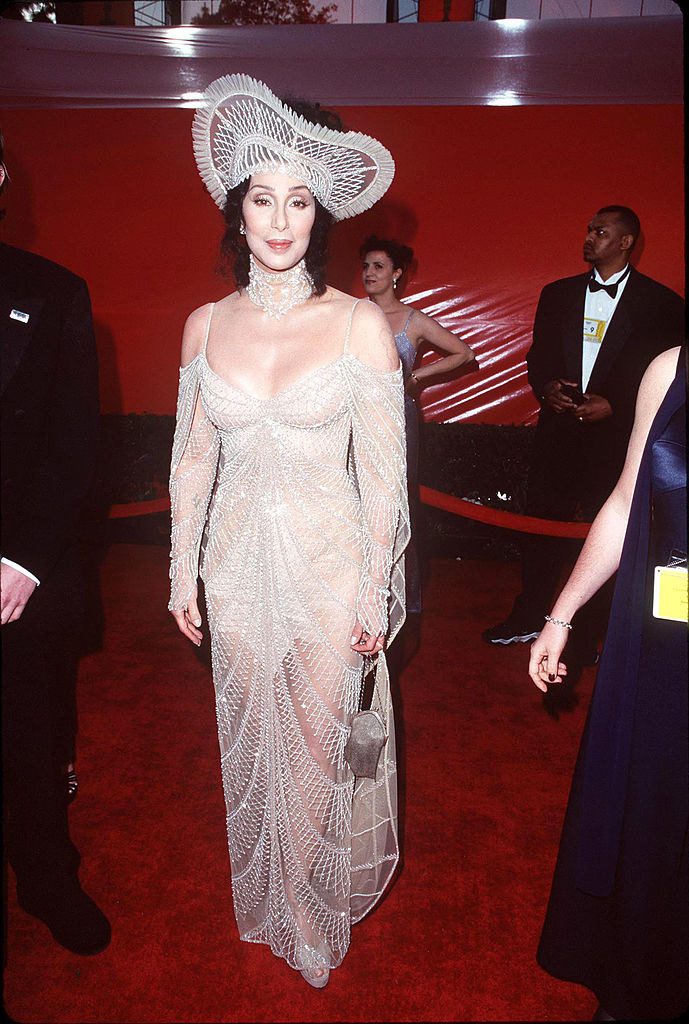 Cher wearing a see-through lace dress with a matching upturned hat