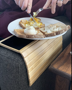 Reviewer using the tray on the arm of a couch to eat a plate of eggs and toast