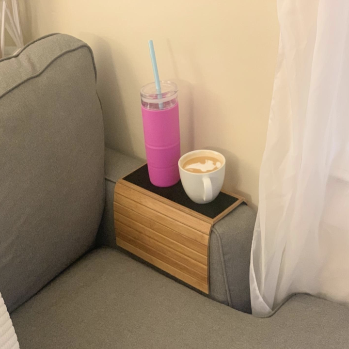 Reviewer using flexible wood tray draped over a couch arm with a mug and water bottle on it