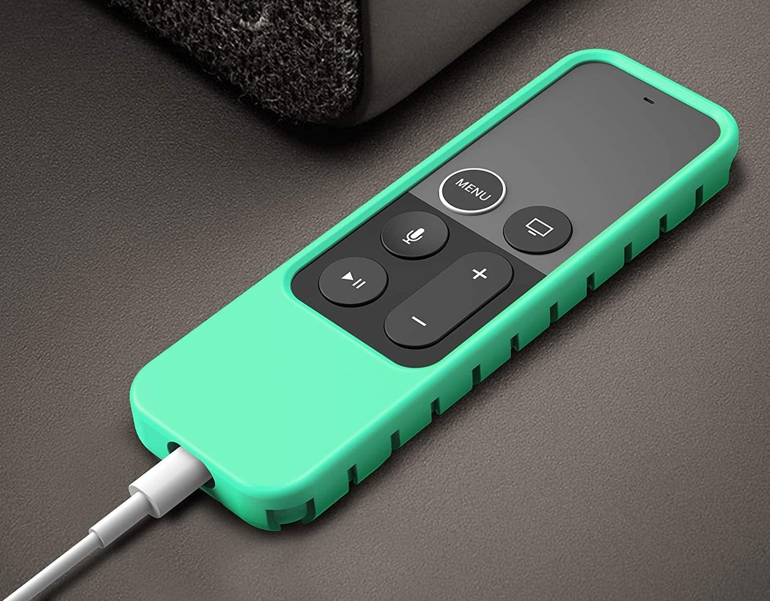 An Apple remote covered by a green silicone casing