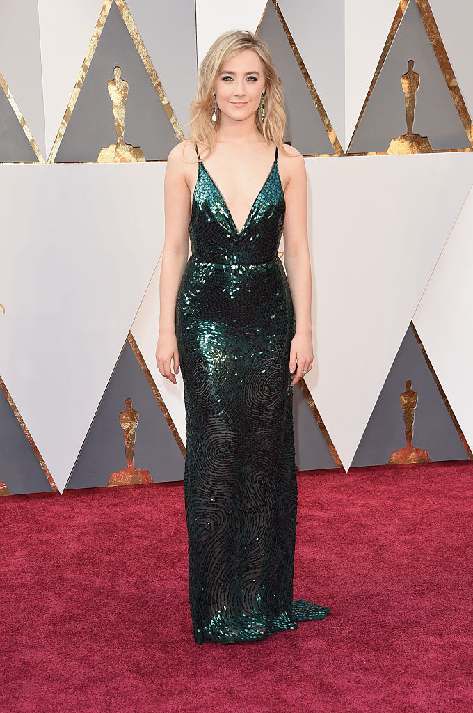 Saoirse in a sparkly form-fitting gown with a deep v-cut and spaghetti straps