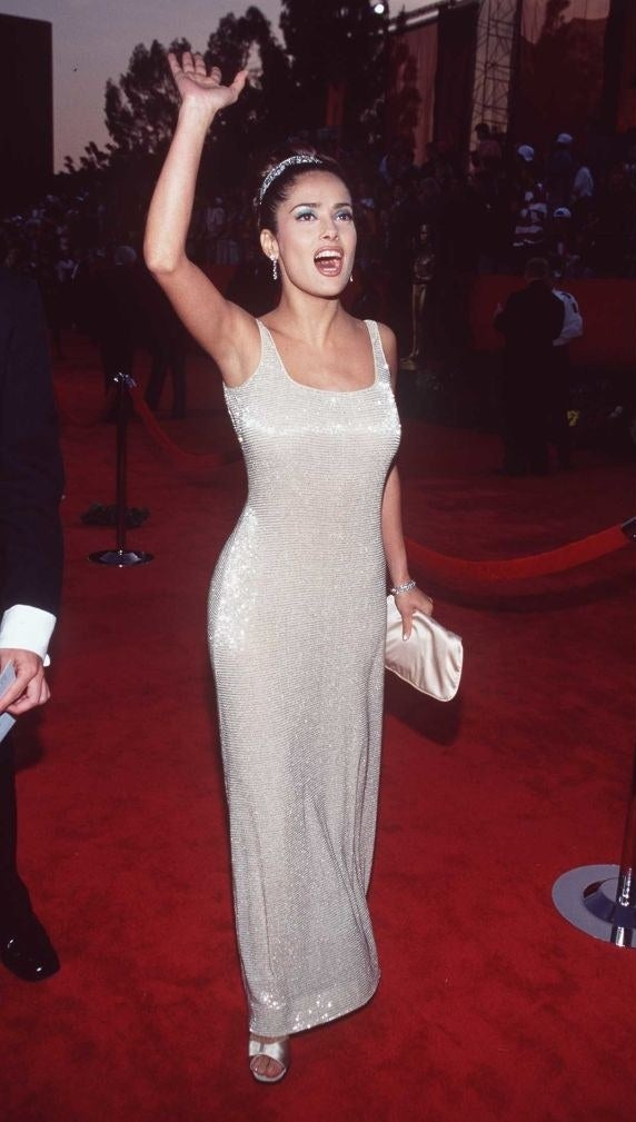 Salma waving in a sparkly gown with her hair up in a bun