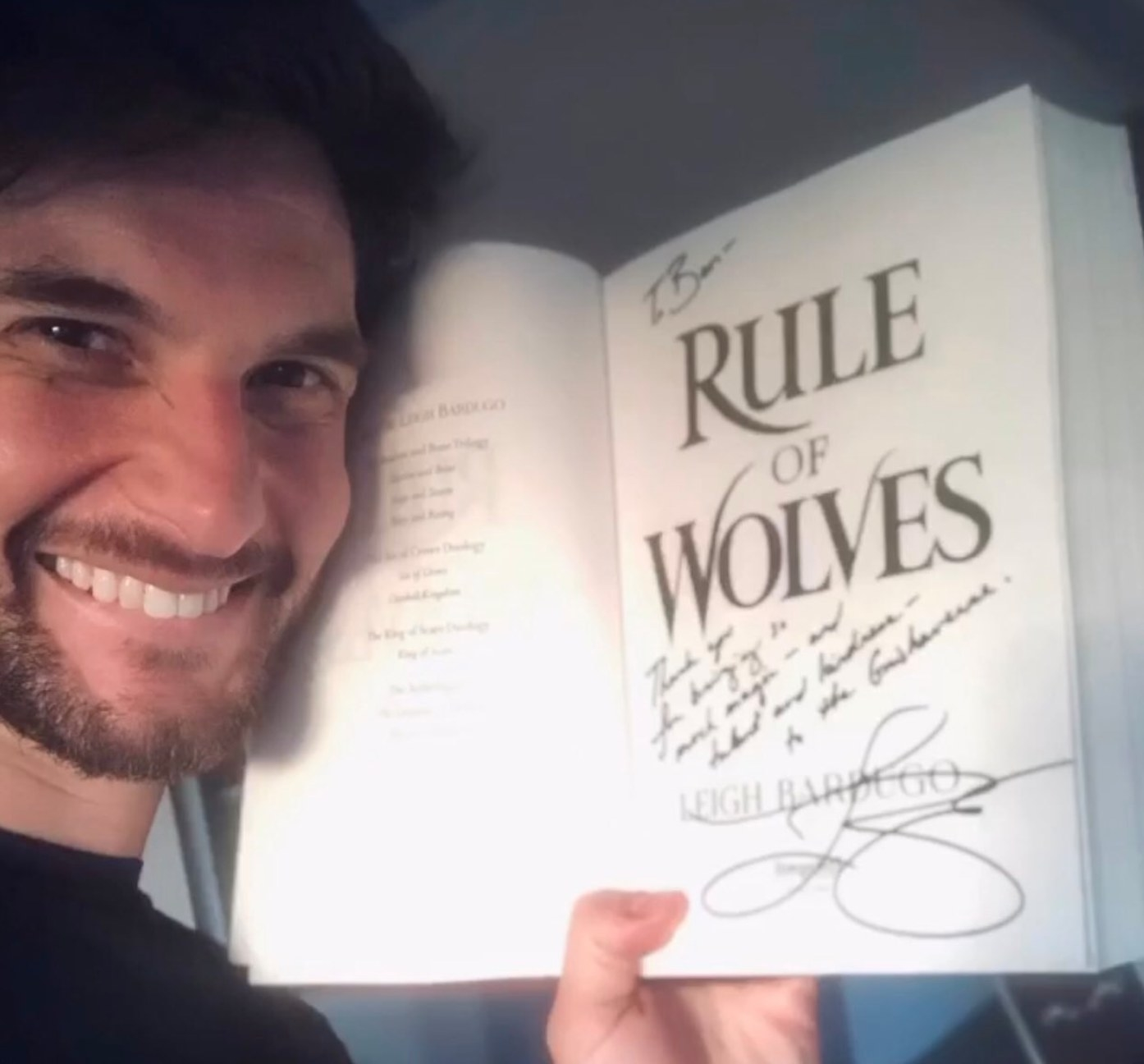 Ben Barnes holding a copy of Rule of Wolves by Leigh Bardugo