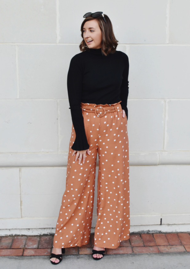 model wearing the tan and white polka dot pants with a black turtleneck and black heels