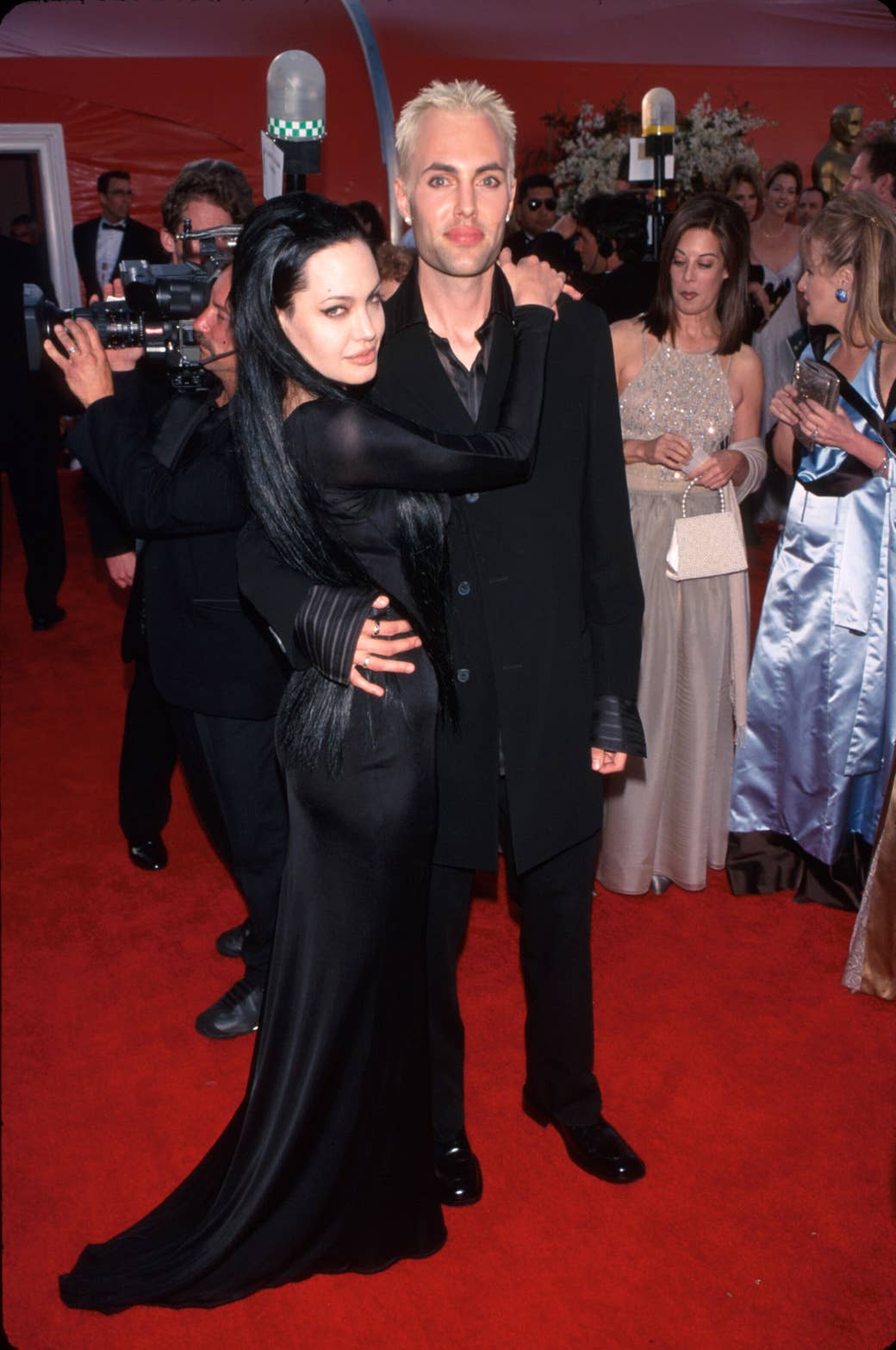 Angelina, wearing a black gown, hugging her brother