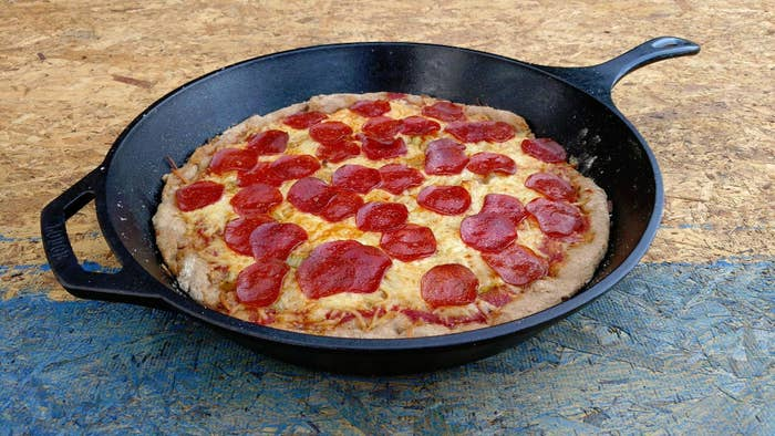the cast iron skillet with a pizza inside
