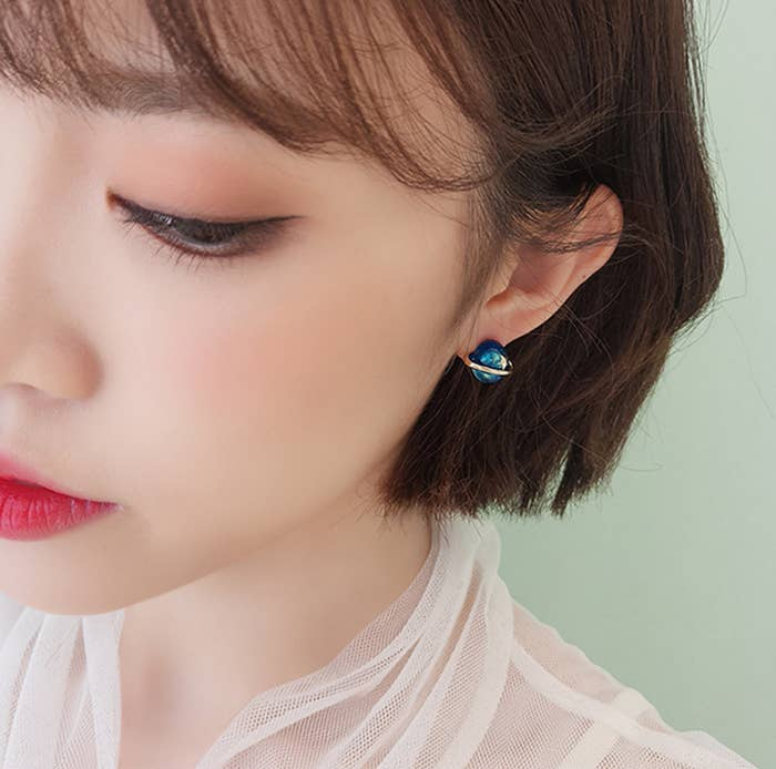 a model wearing the blue planet themed earring studs