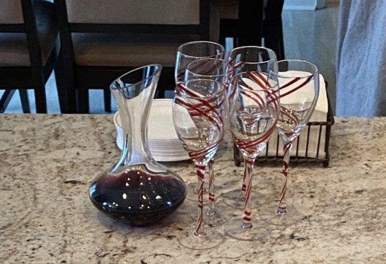 a reviewer showcasing their carafe filled with wine next to wine glasses