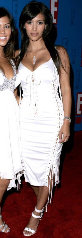 Kim wearing a tight, strappy white dress, with lace-up details on the side