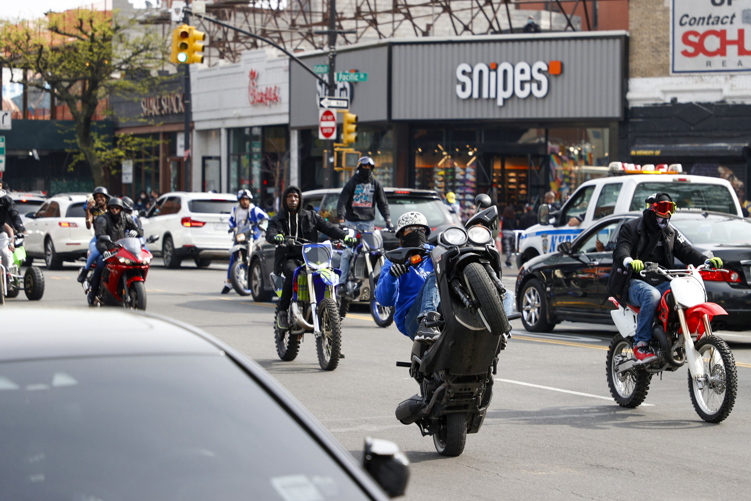 One motorcyclist does a wheelie on the streets of Brooklyn