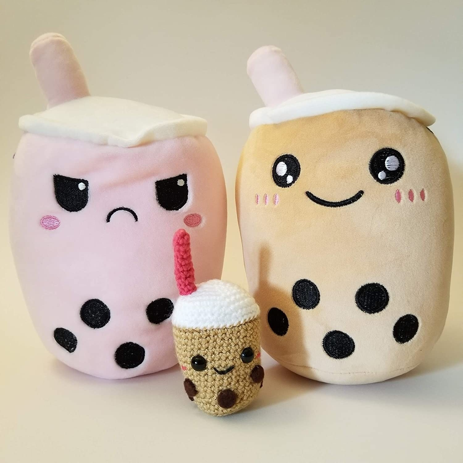 the reversible boba plushie showing the sad pink boba and happy brown boba with a crocheted boba in between the two