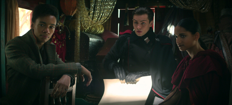 KIT YOUNG as JESPER FAHEY, FREDDY CARTER as KAZ BREKKER and AMITA SUMAN as INEJ GHAFA in SHADOW AND BONE. Kaz rolling a map.