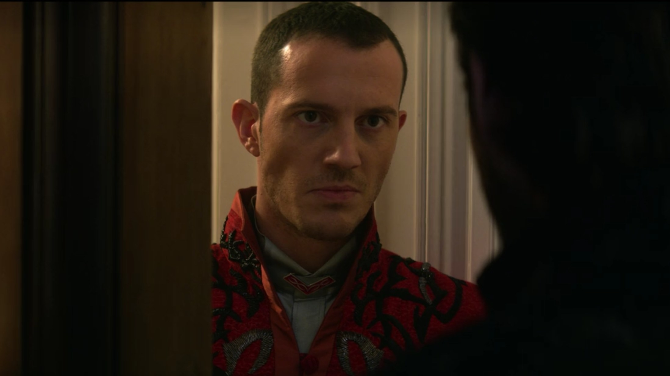 Simon Sears as Ivan standing at the door with bad news.