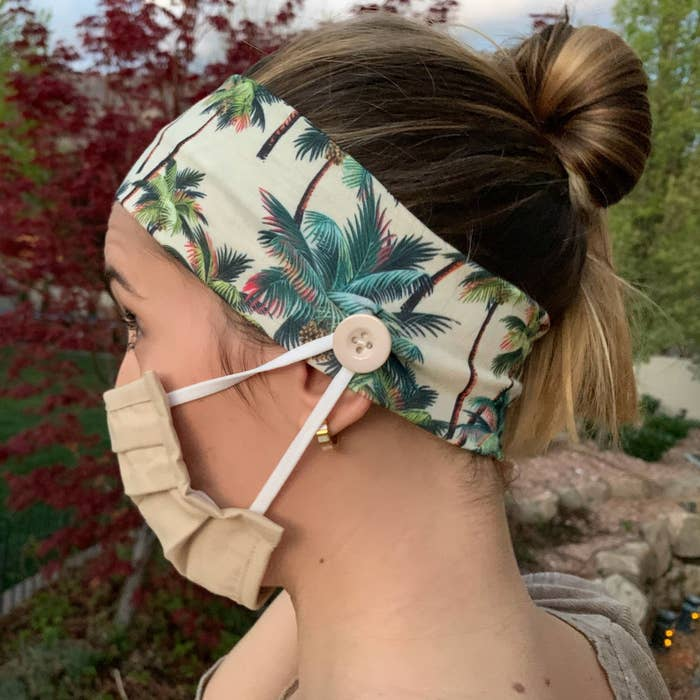 person wearing a face mask with the ear loop attached around a button that's on a headband
