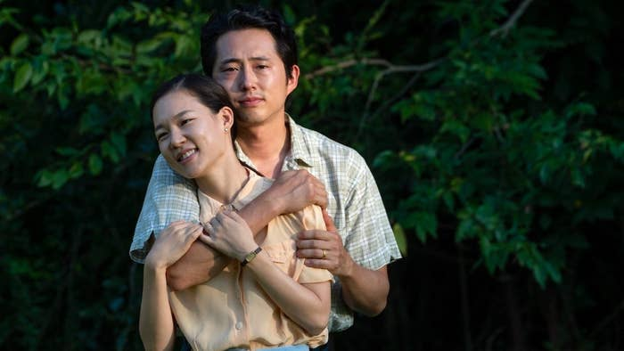 """Jacob standing behind Monica (from """"Minari"""") with his arm around her. They are standing in front of a dark green bush."""