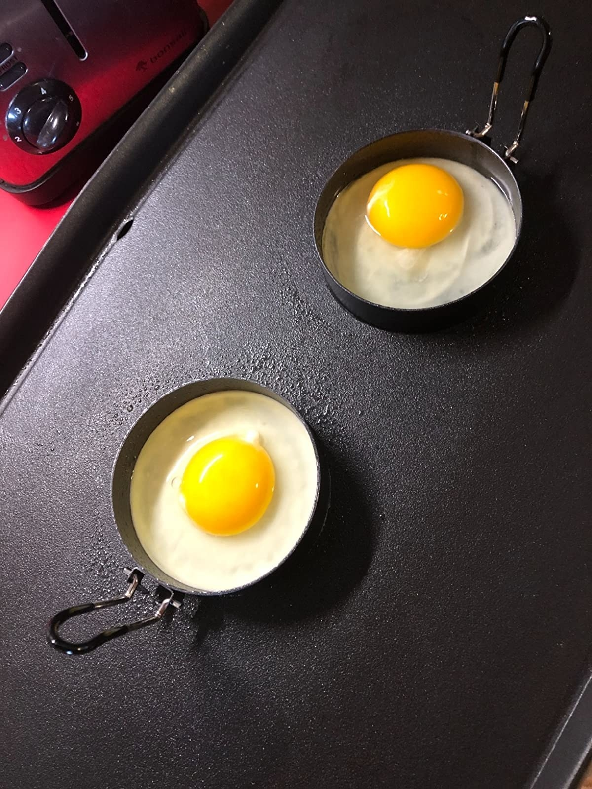 two eggs in the molds on a griddle