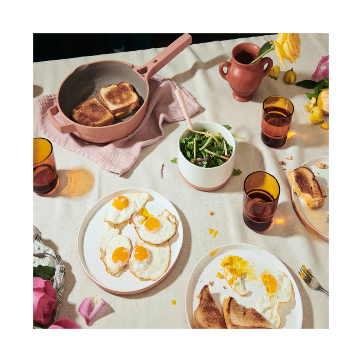 a table full of fried eggs on a plate and other breakfast things