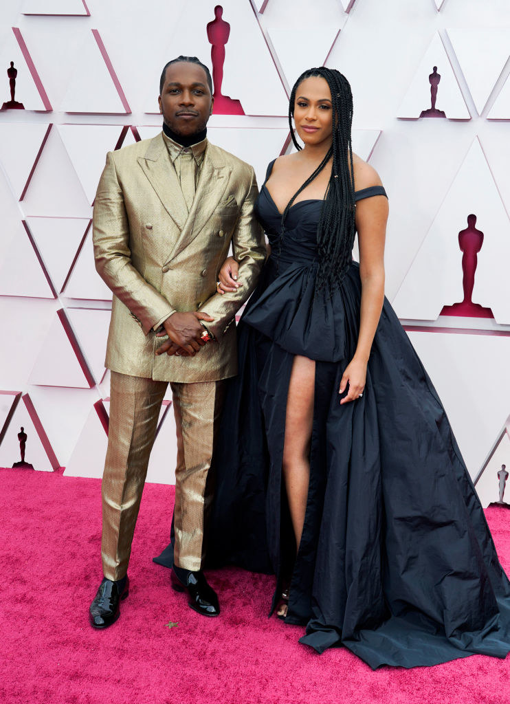 Leslie in a metallic gold suit and his wife in a sweetheart ball gown