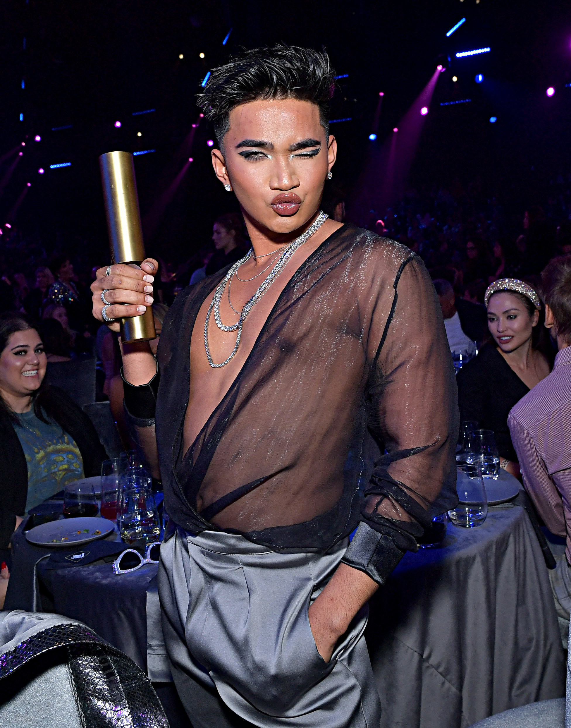 Bretman holding his award and posing for a photo
