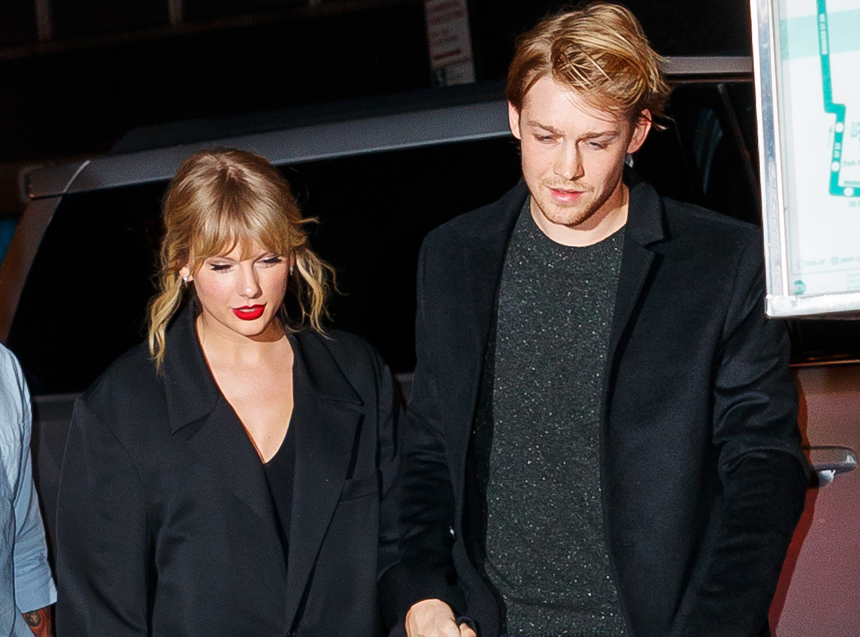 Taylor and Joe hold hands while exiting their car