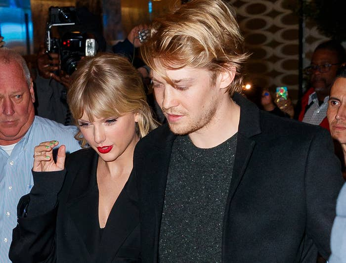 Joe and Taylor hold on to each other while leaving an event