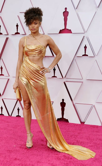 Andra wore a gold metallic gown with cutouts and an updo