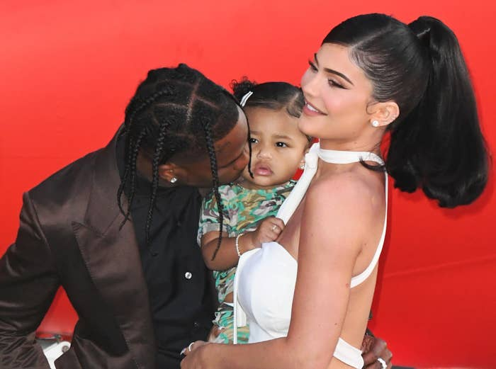 Travis kisses Stormi while Kylie holds her