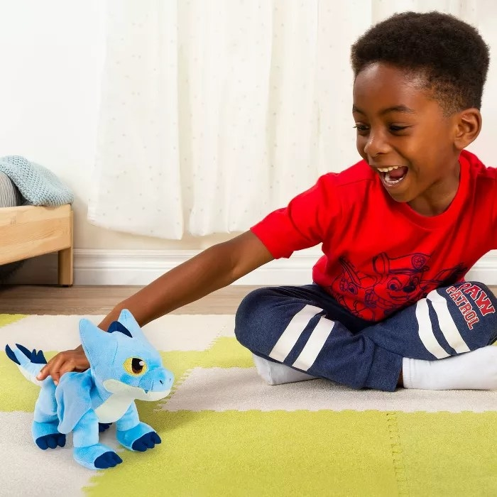 A child playing with the dragon doll
