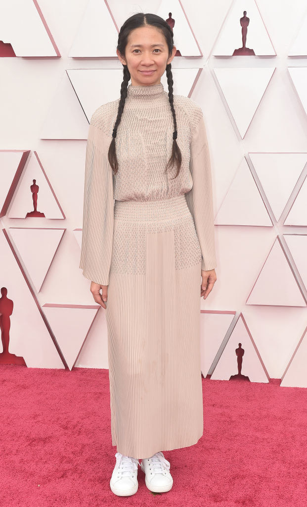 Chloé Zhao in pigtails and wearing a beige long-sleeved, high-neck gown with white sneakers