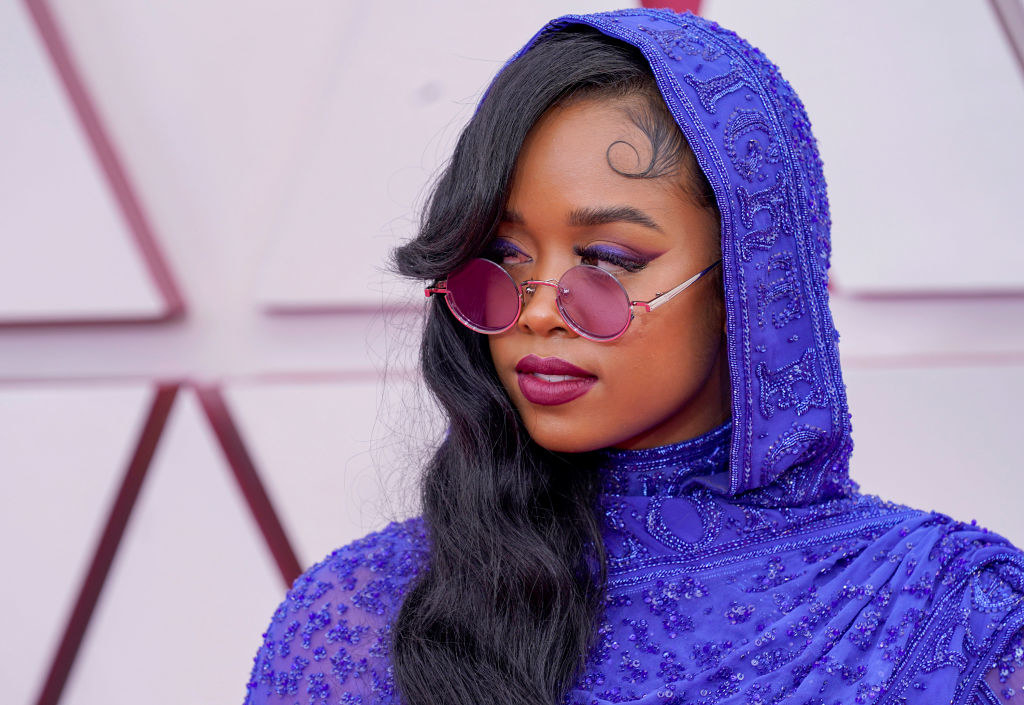 H.E.R. in a blue hooded outfit and wearing sunglasses