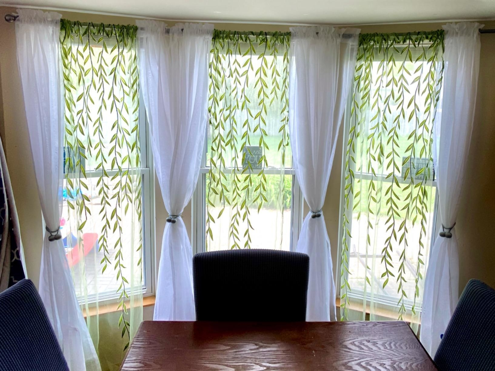 Reviewer drapes hanging on three windows