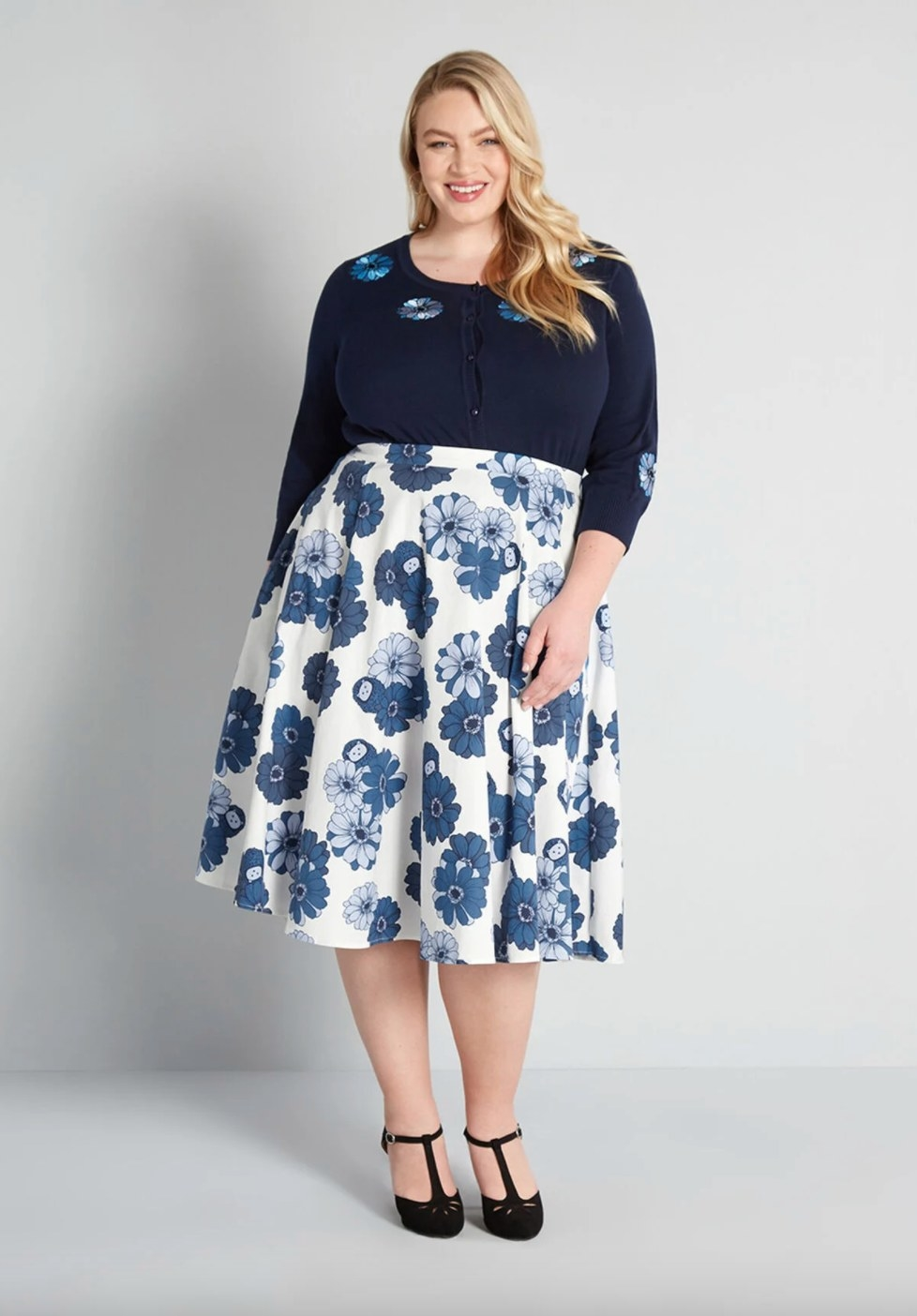 Model wearing a midi skirt with white and blue flowers