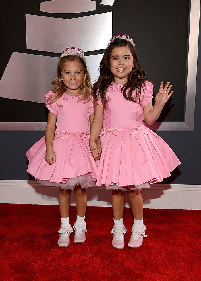 Sophia Grace and Rosie in matching frilly dresses, Mary Jane shoes, and tiaras