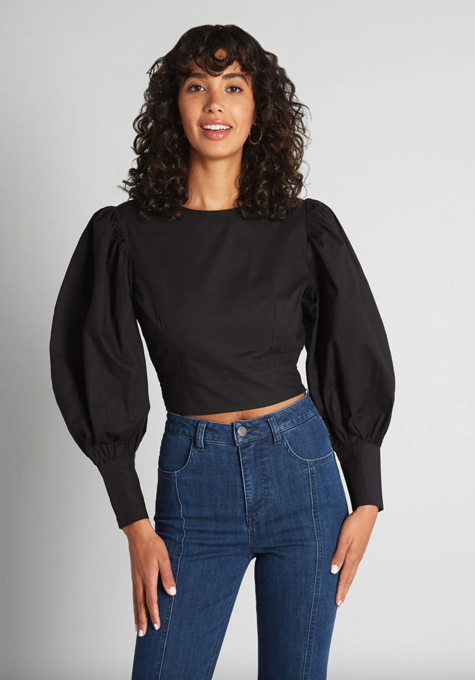 The cropped blouse in black on a model wearing high waisted jeans