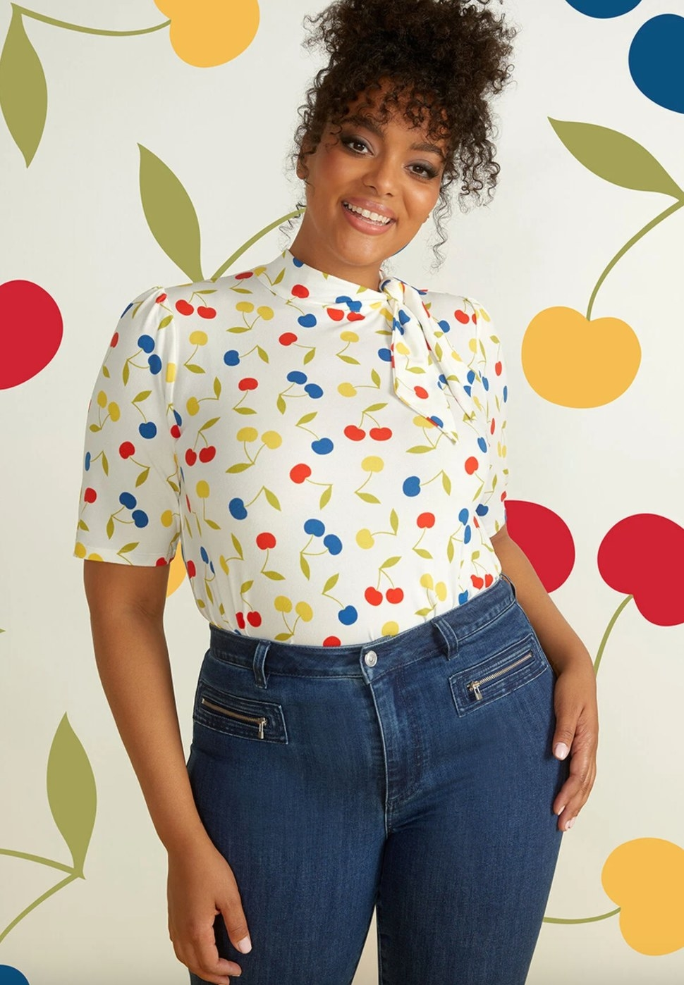 The tie-neck top in white cherry print on a model