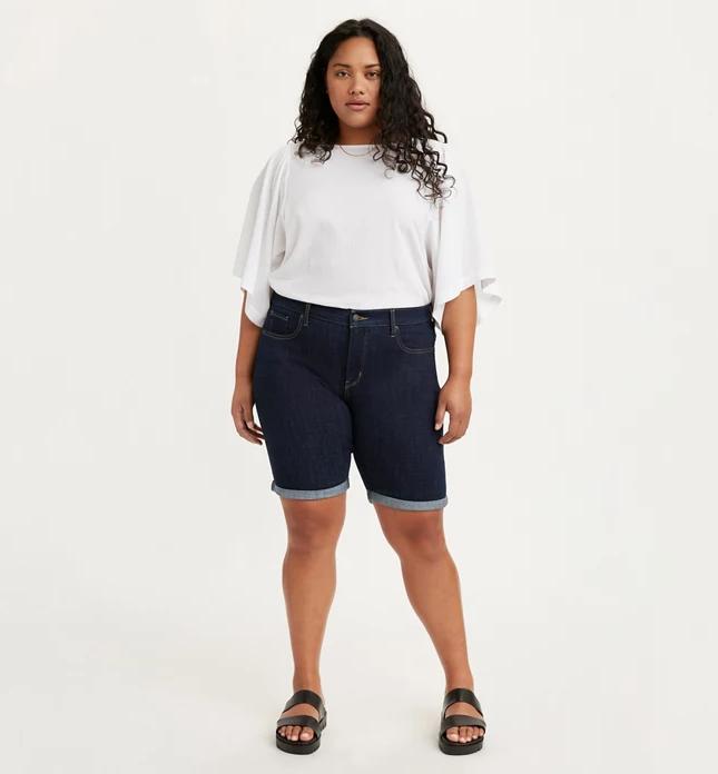A model wearing the shaping Bermuda denim shorts in the dark wash