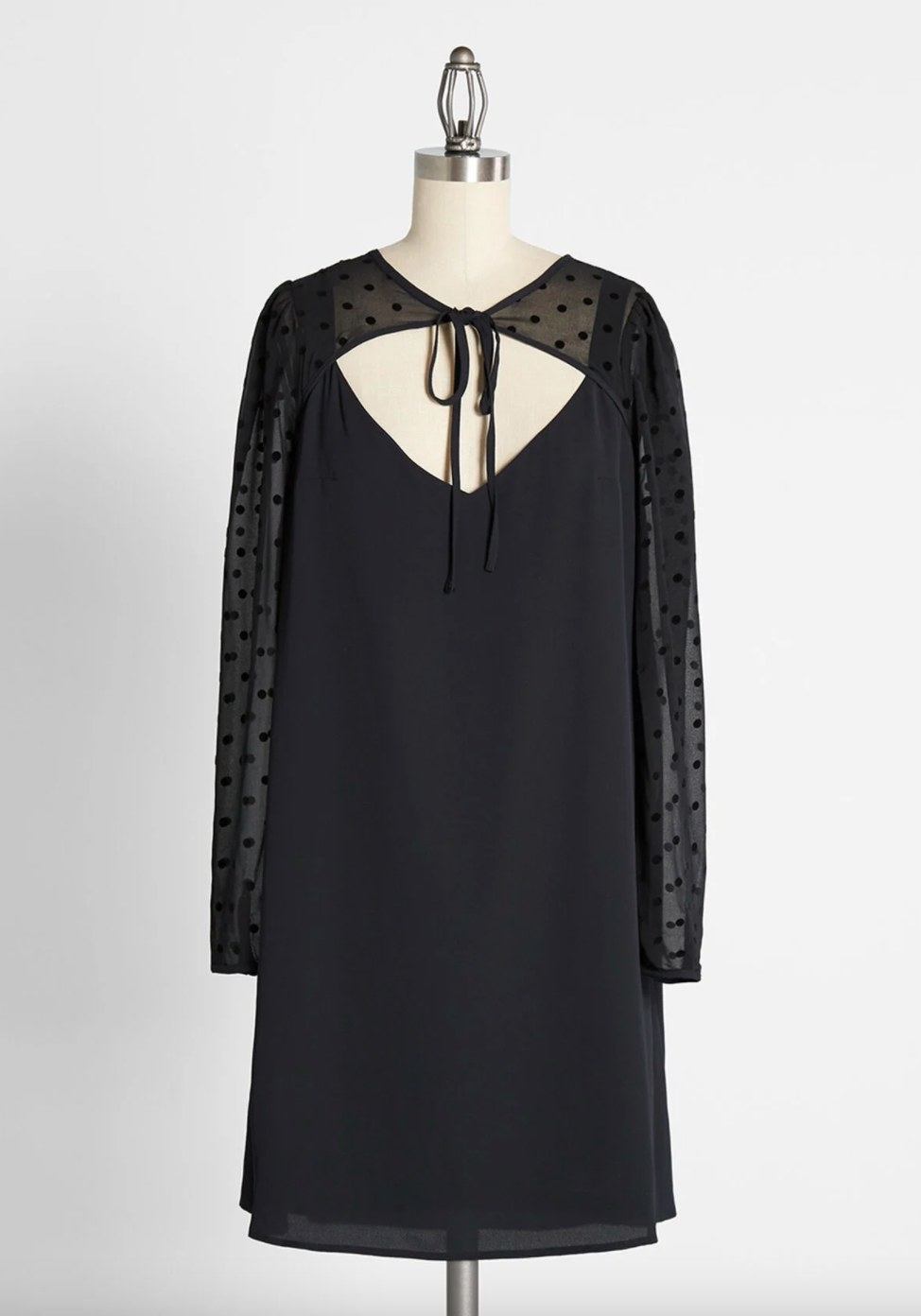 The shift dress in black with a front tie and sheer dotted sleeves