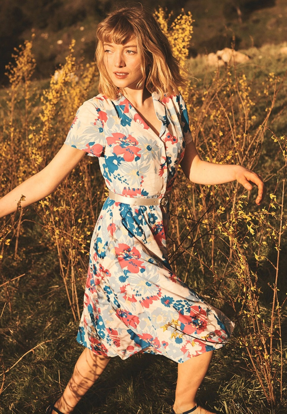 The white, blue, and coral floral shirt dress worn by a model