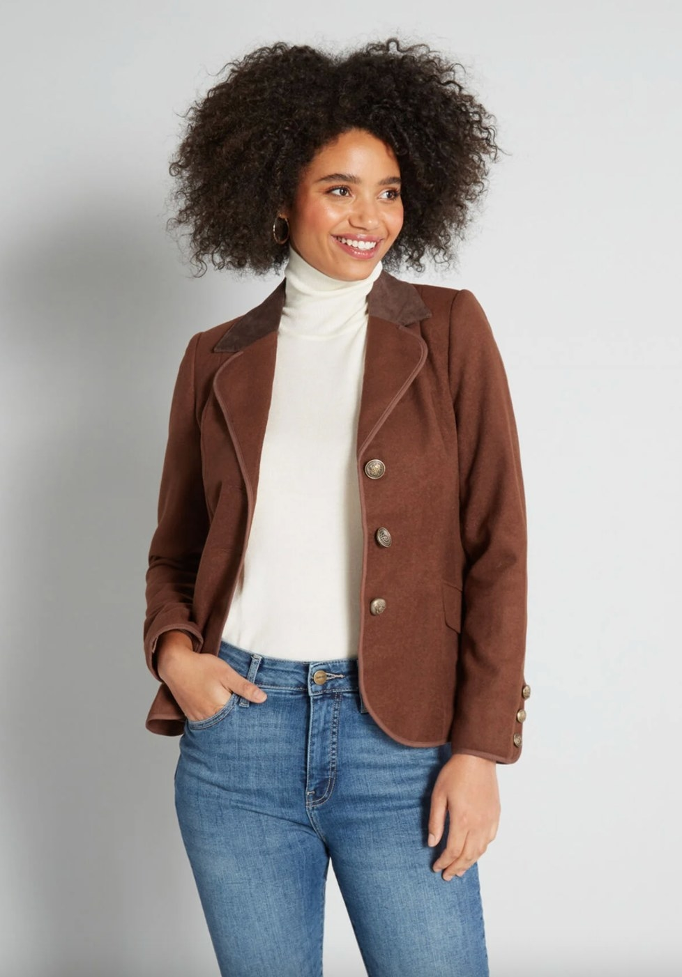 The blazer in brown on a model wearing a white turtleneck