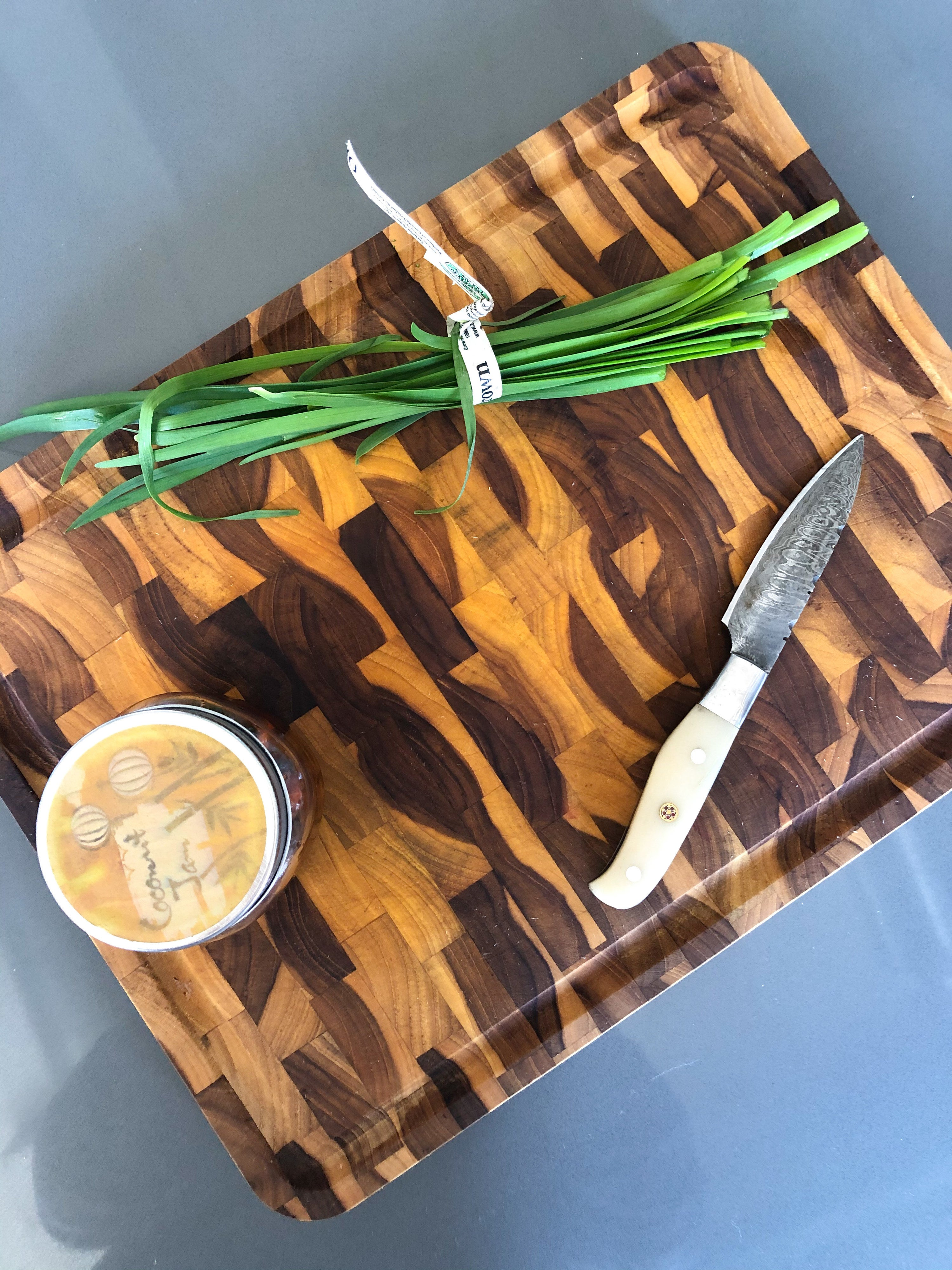 A flatlay of the end-grain butcher block cutting board with a chic knife and fresh herbs on top