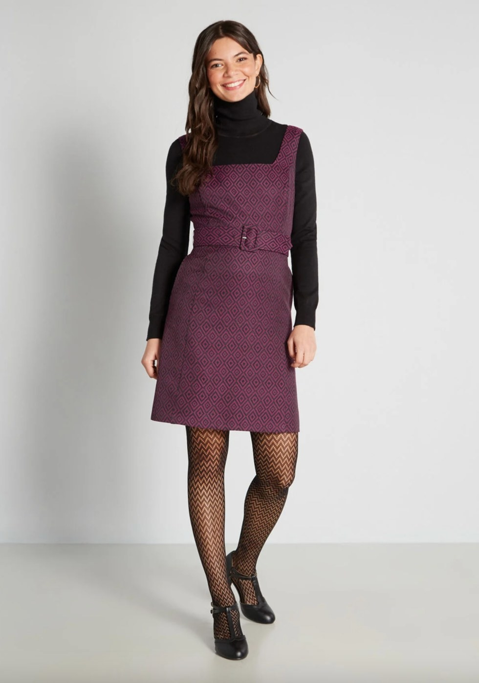 The fit and flare dress in purple on a model wearing patterened stockings