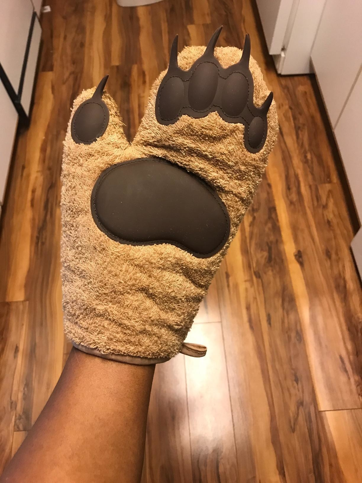 a reviewer wearing an oven mitt that looks like a bear claw
