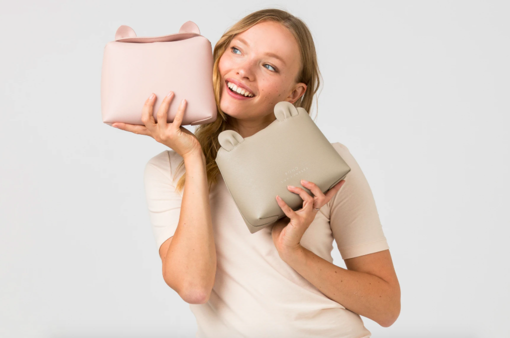 A model holding two of the crossbody bags