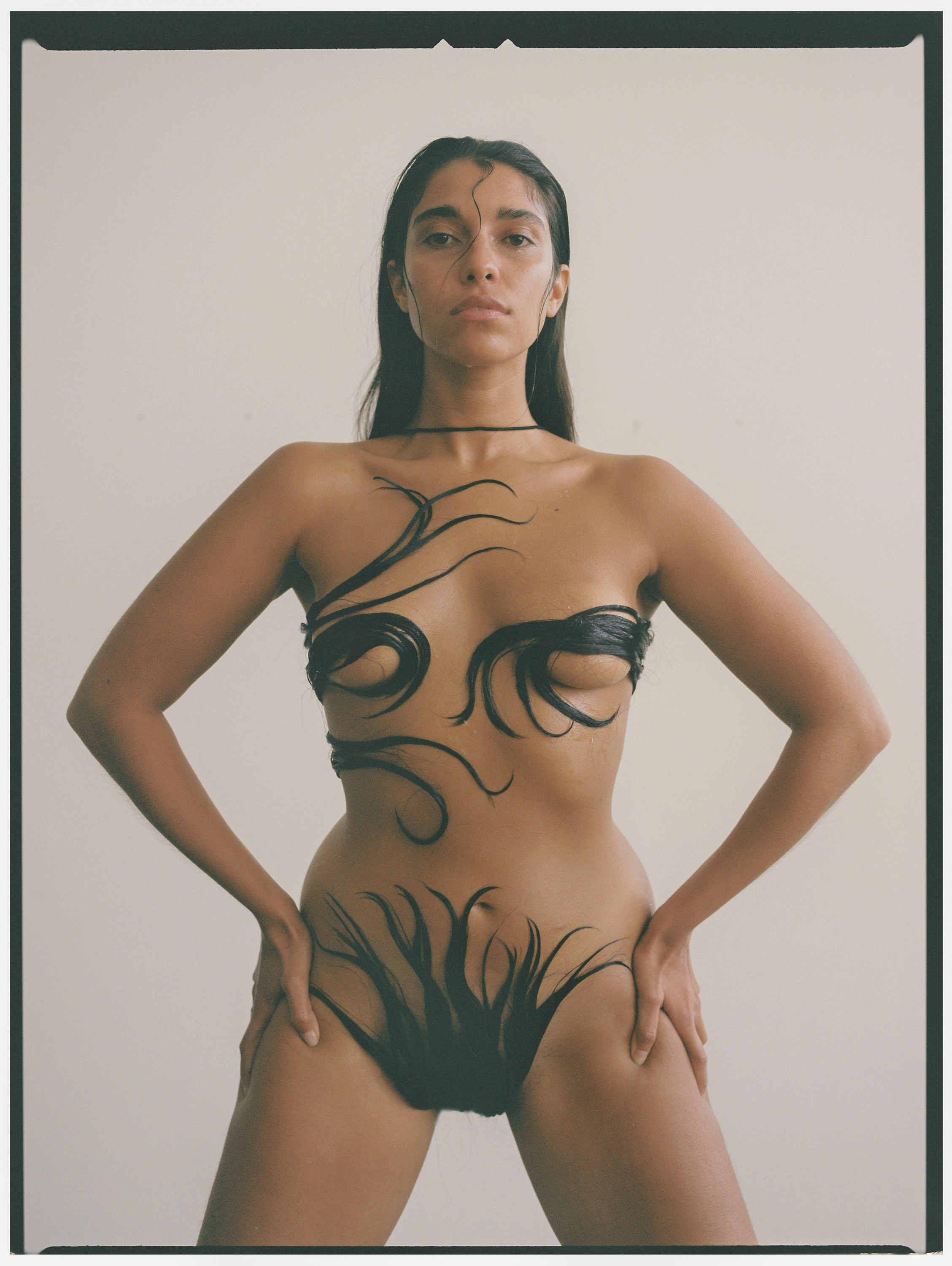 A woman posed naked with her hair covering her breasts