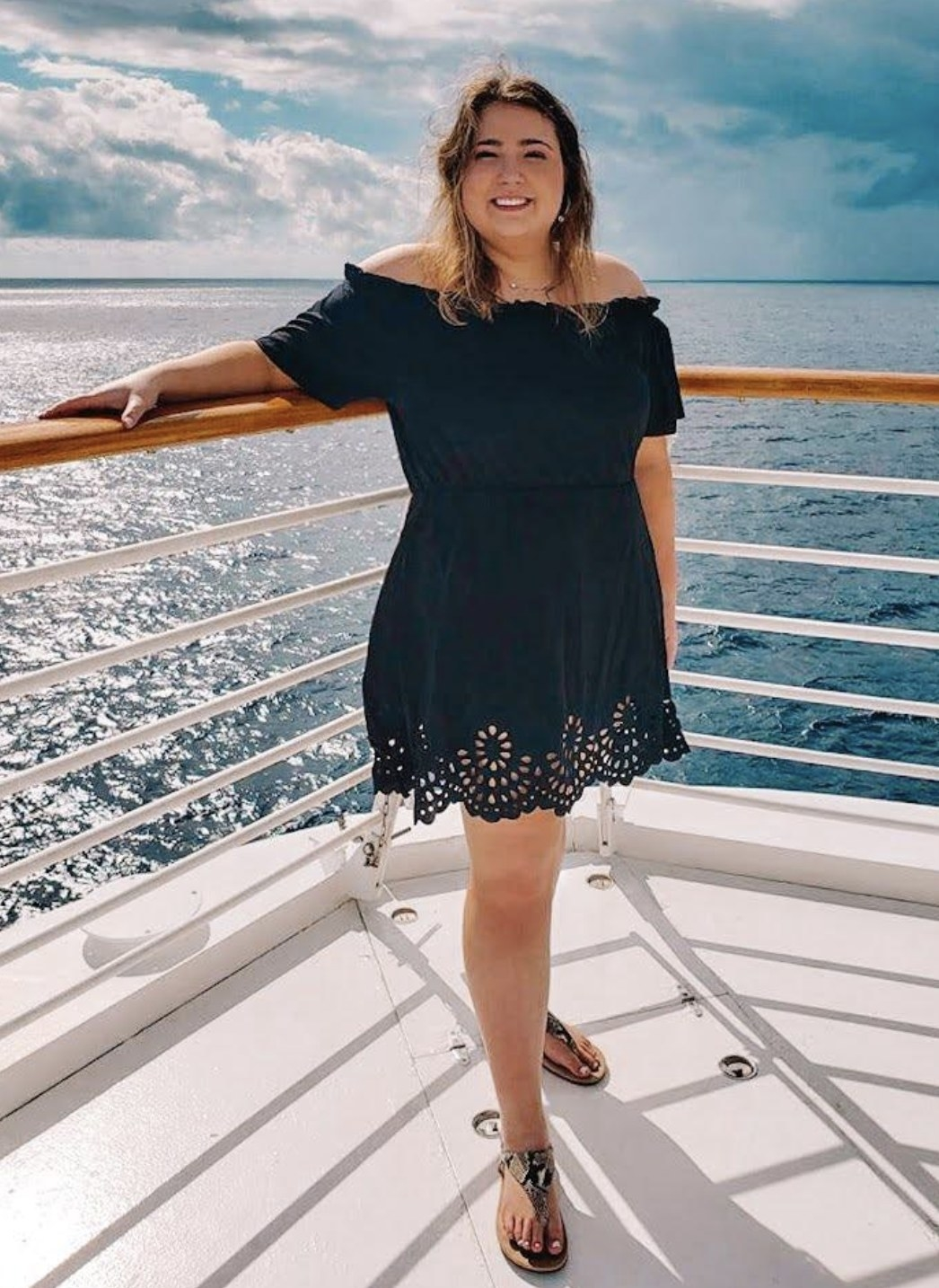 a model wearing the dress in black with sandals on a boat