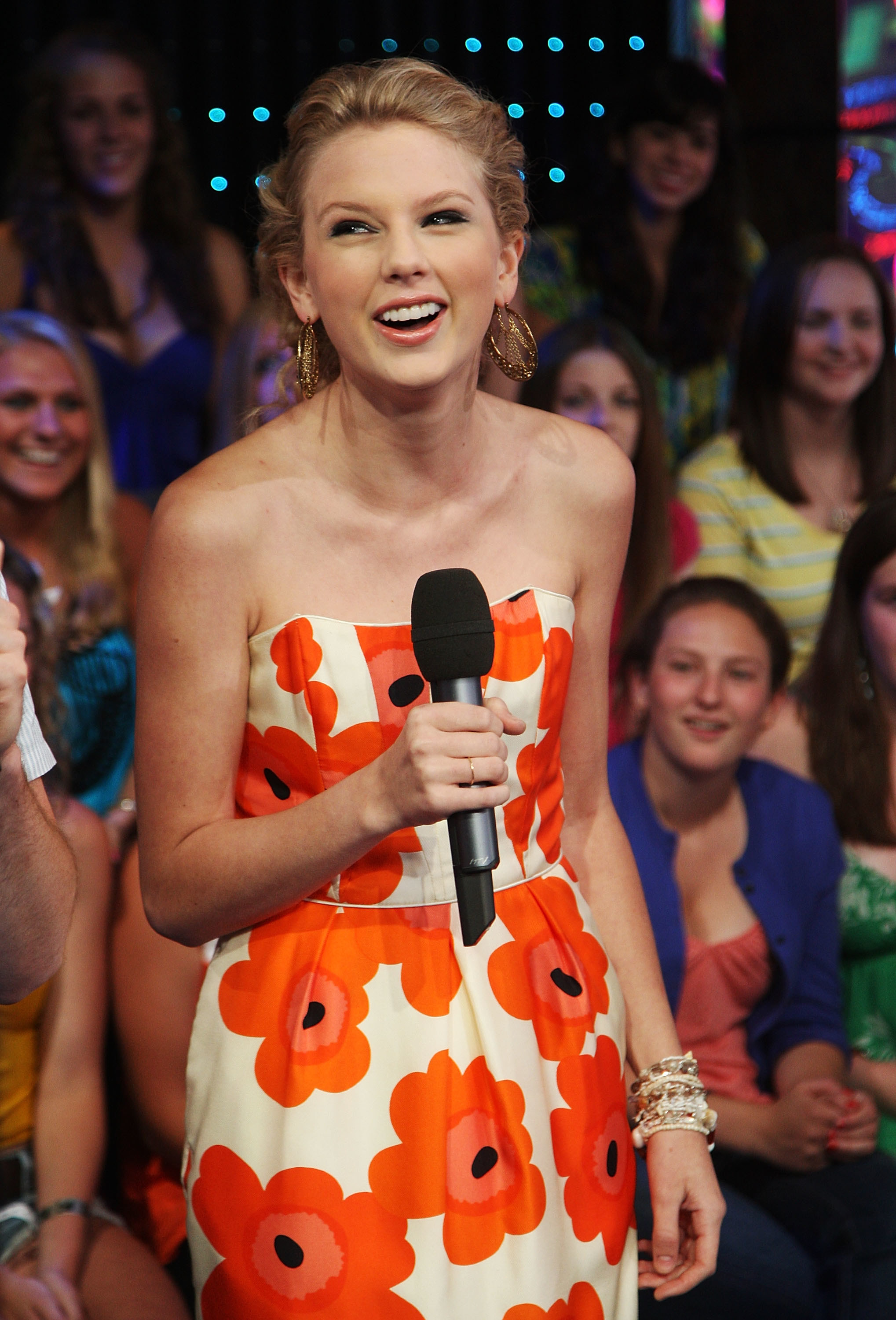 Taylor Swift in an orange floral strapless dress