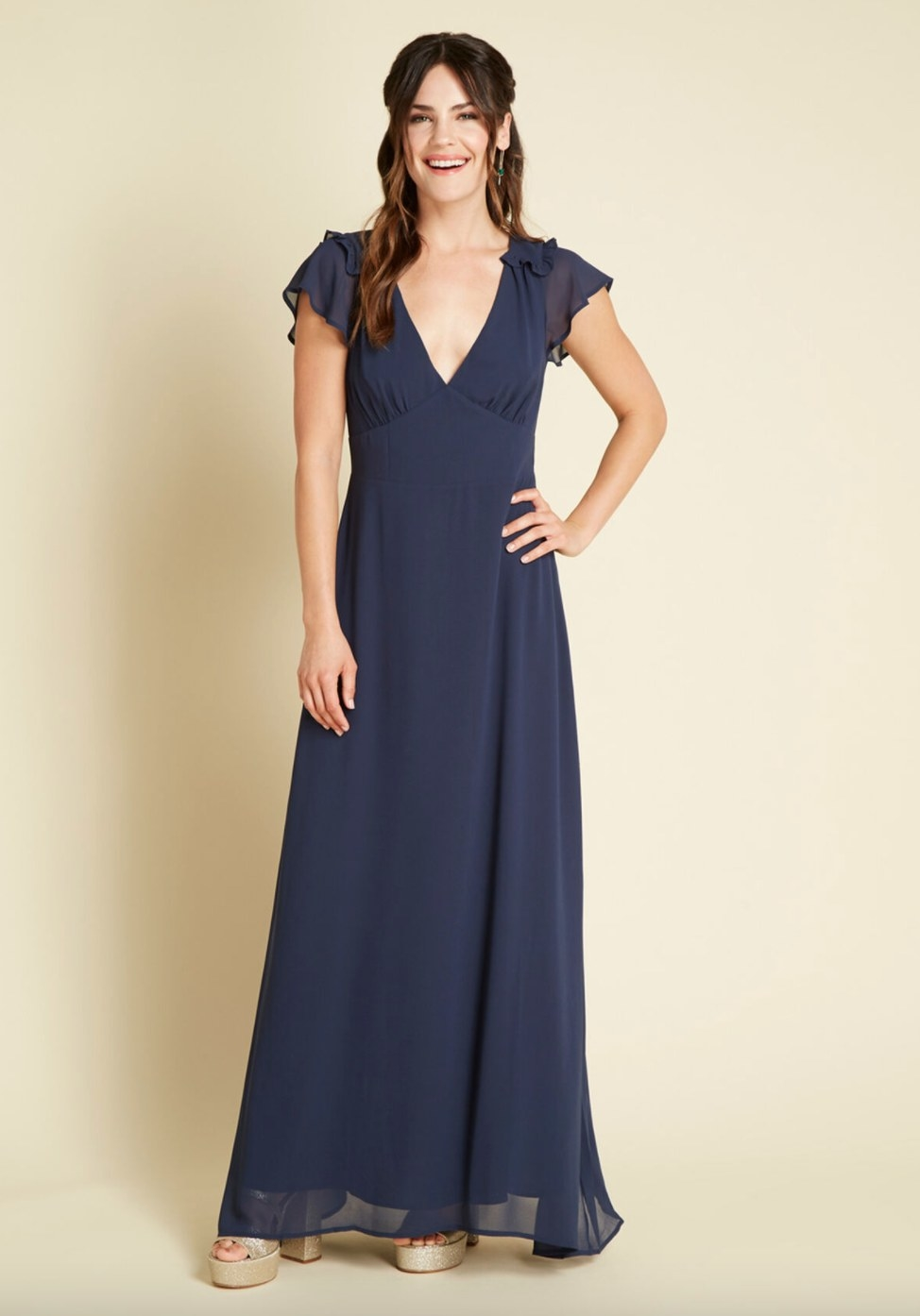 The flow maxi dress in navy being worn by a model in platform heels