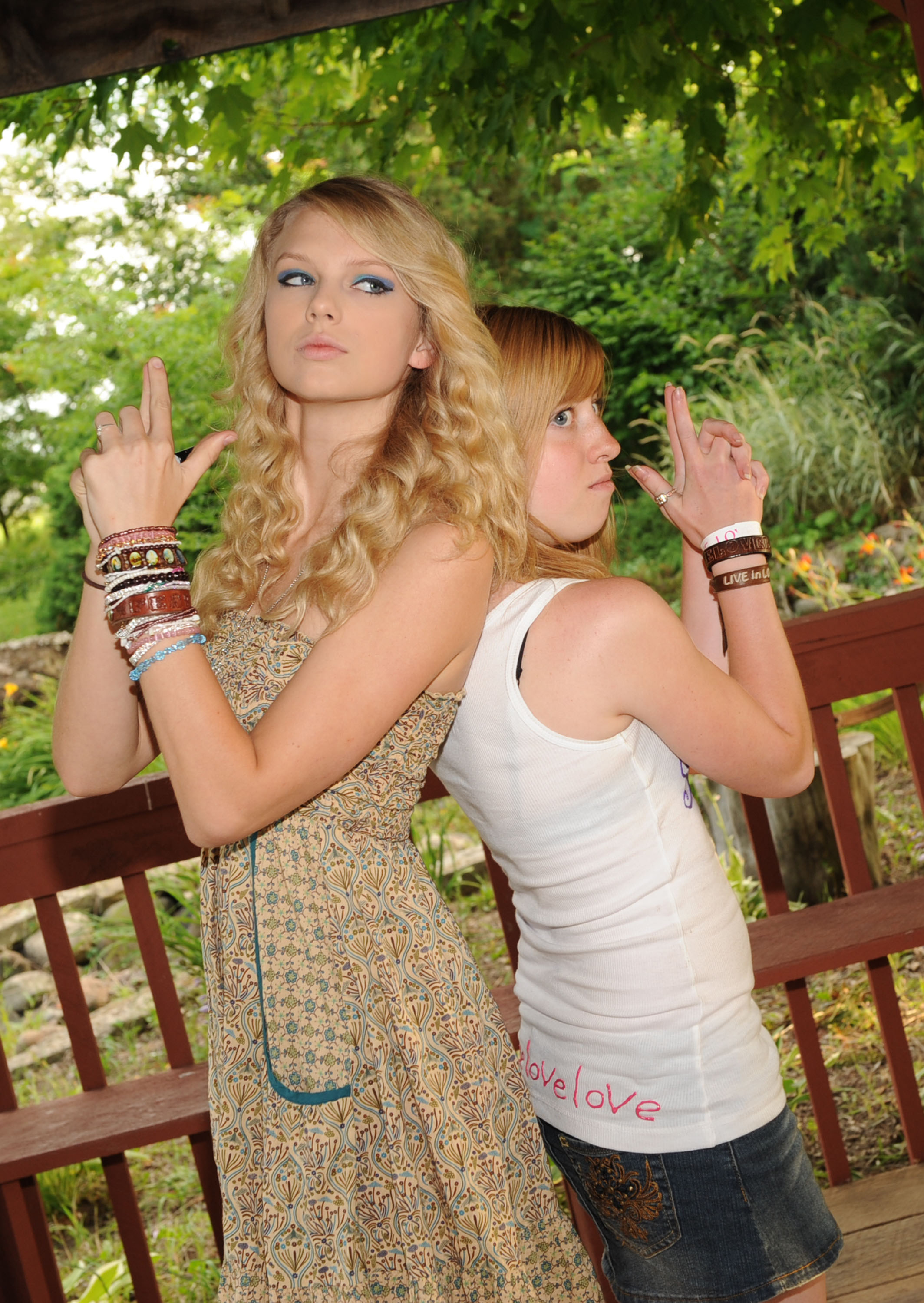 Taylor Swift posing with a fan back to back