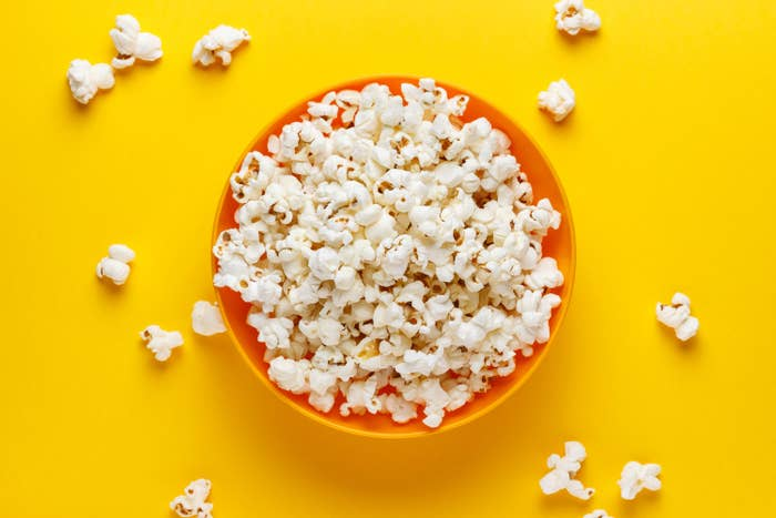 An image of popcorn in a bowl over a yellow background